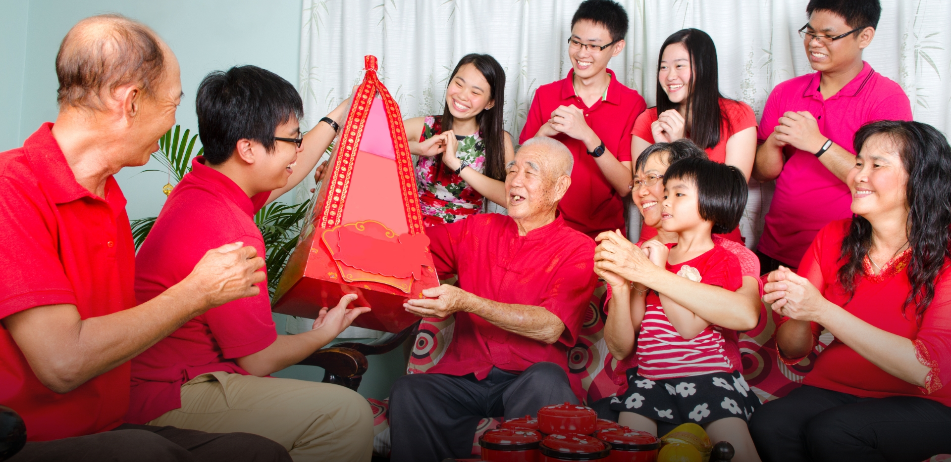 Asian family all dressed in red and gold surround grandfather as grandson gives him a gift commemorating traditional holiday