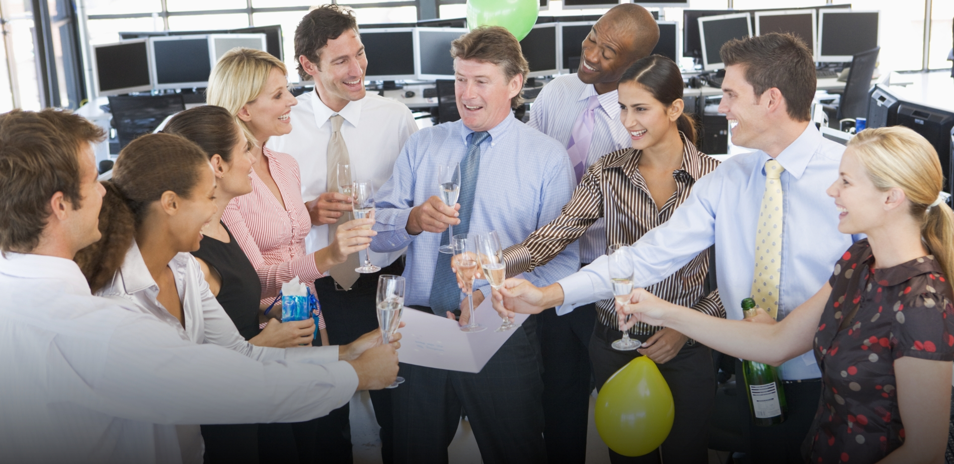 corporate team at work pops bottle of champagne to celebrate a big deal