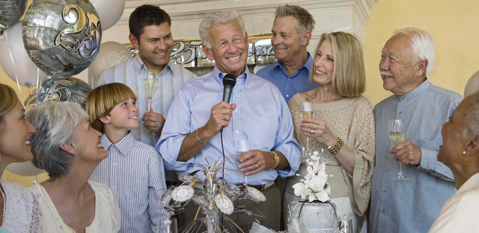 older couple surrounded by friends and family raise glass of champagne to celebrate 25th wedding anniversary