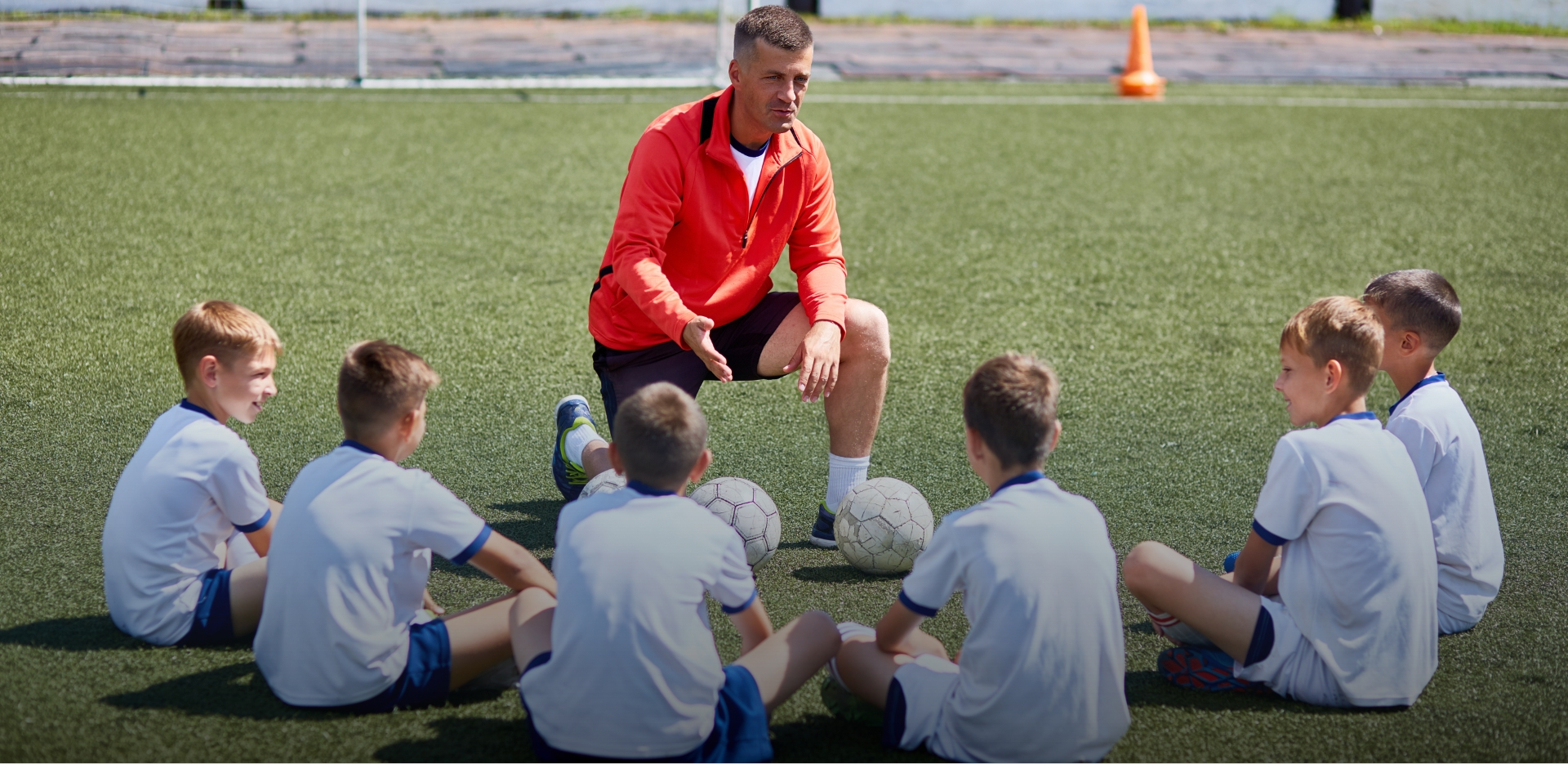 adolescent boys soccer team surround coach as he takes a knee to offer words of guidance