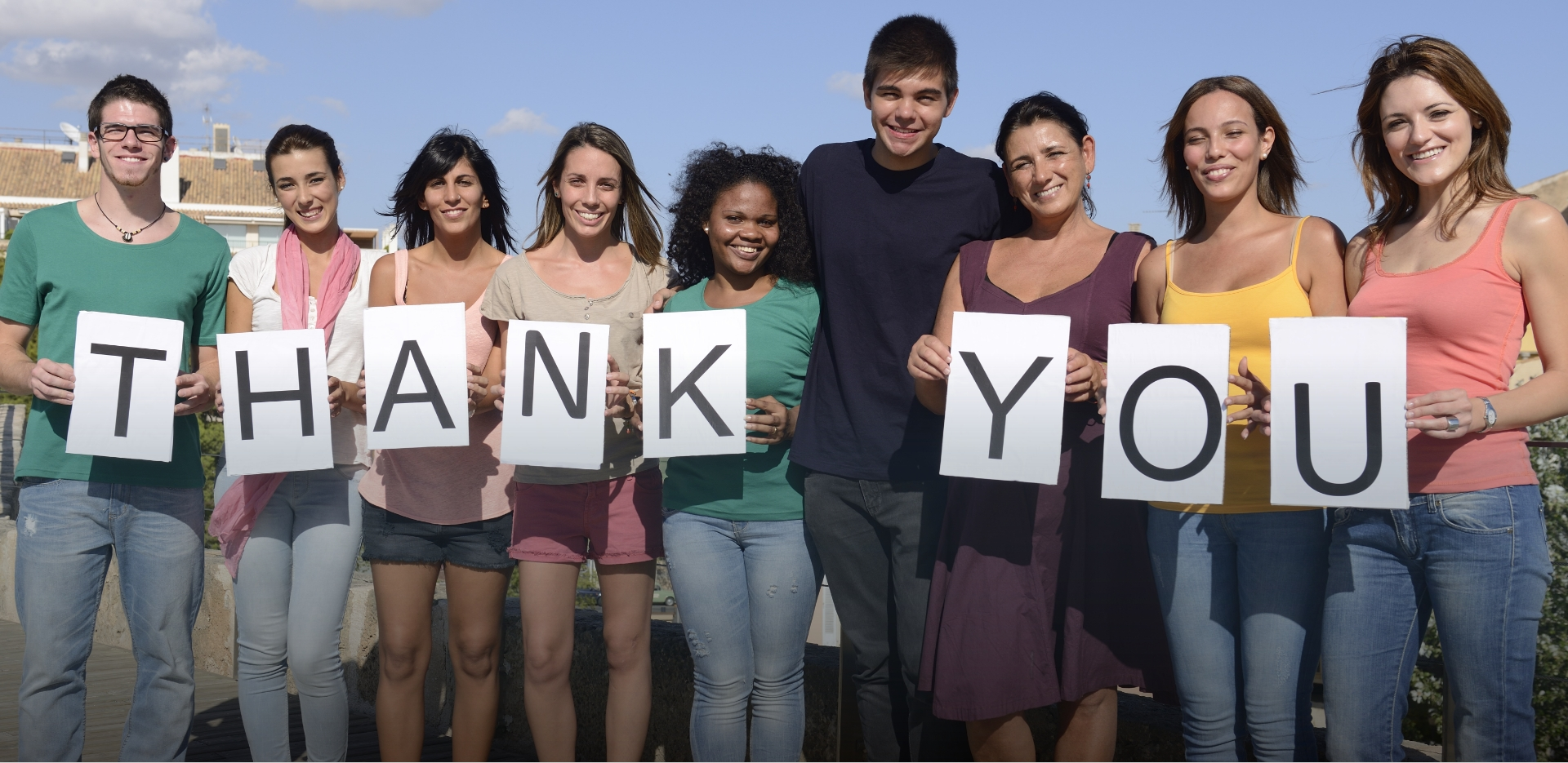 group of smiling young adults hold letters that spell THANK YOU in gratitude