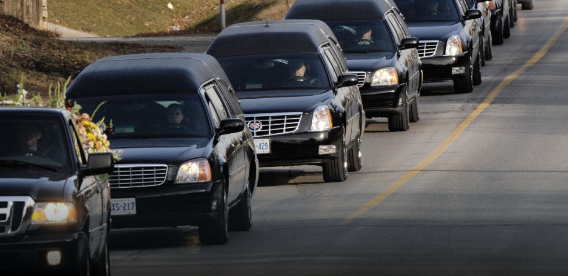 long row of black limosines follow hearse with stacks of flowers to a funeral