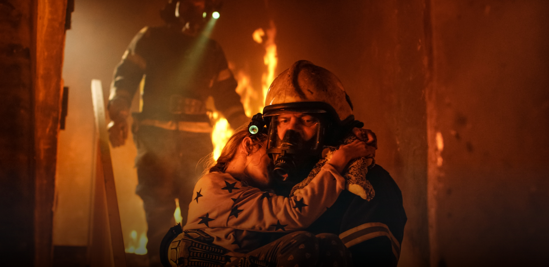 a firefighter carries a young girl wearing pajamas and holding a stuffed animal out of a burning house at night