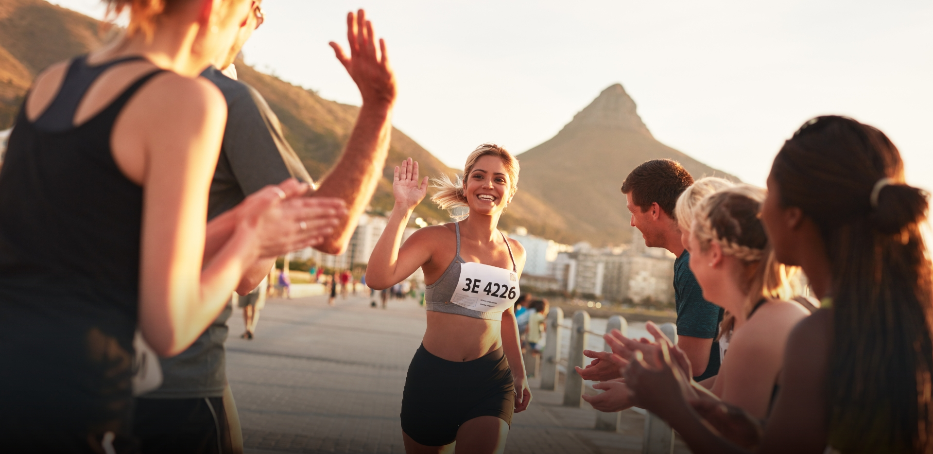 a bunch of friends high five and cheer for a female runner as she passes them during a marathon race