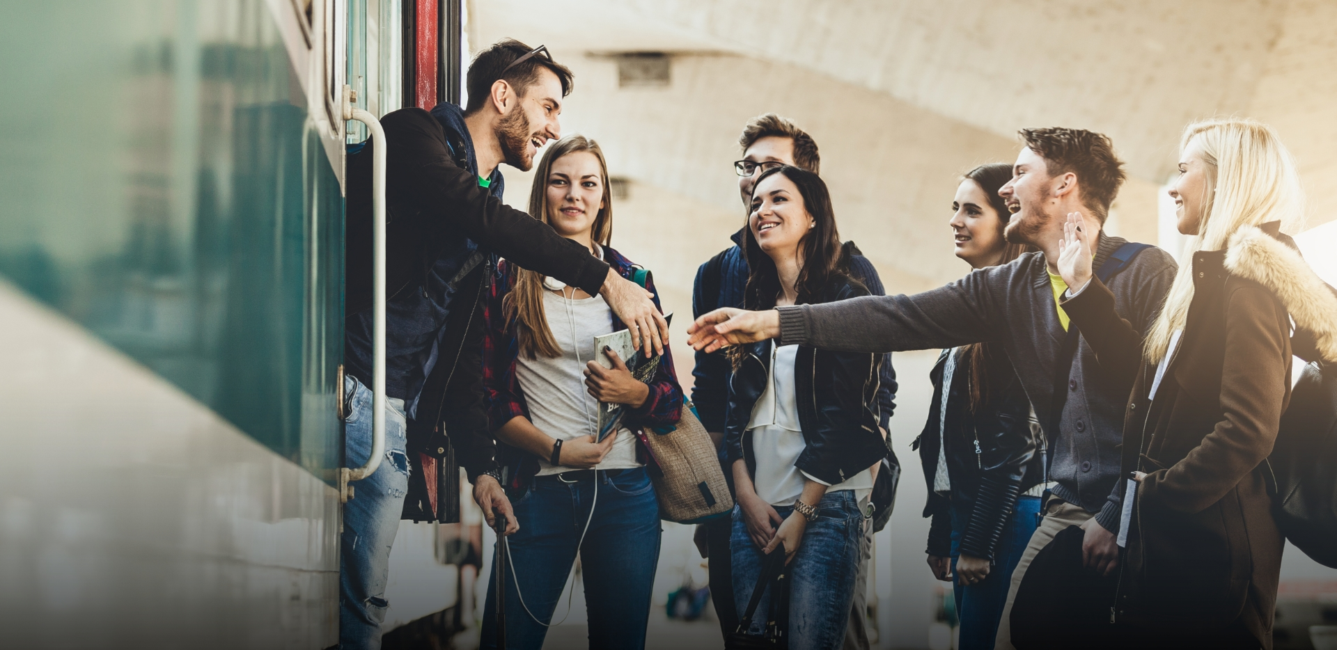 big group of young adults gather at train station to bid a happy farewell to friend who is leaving