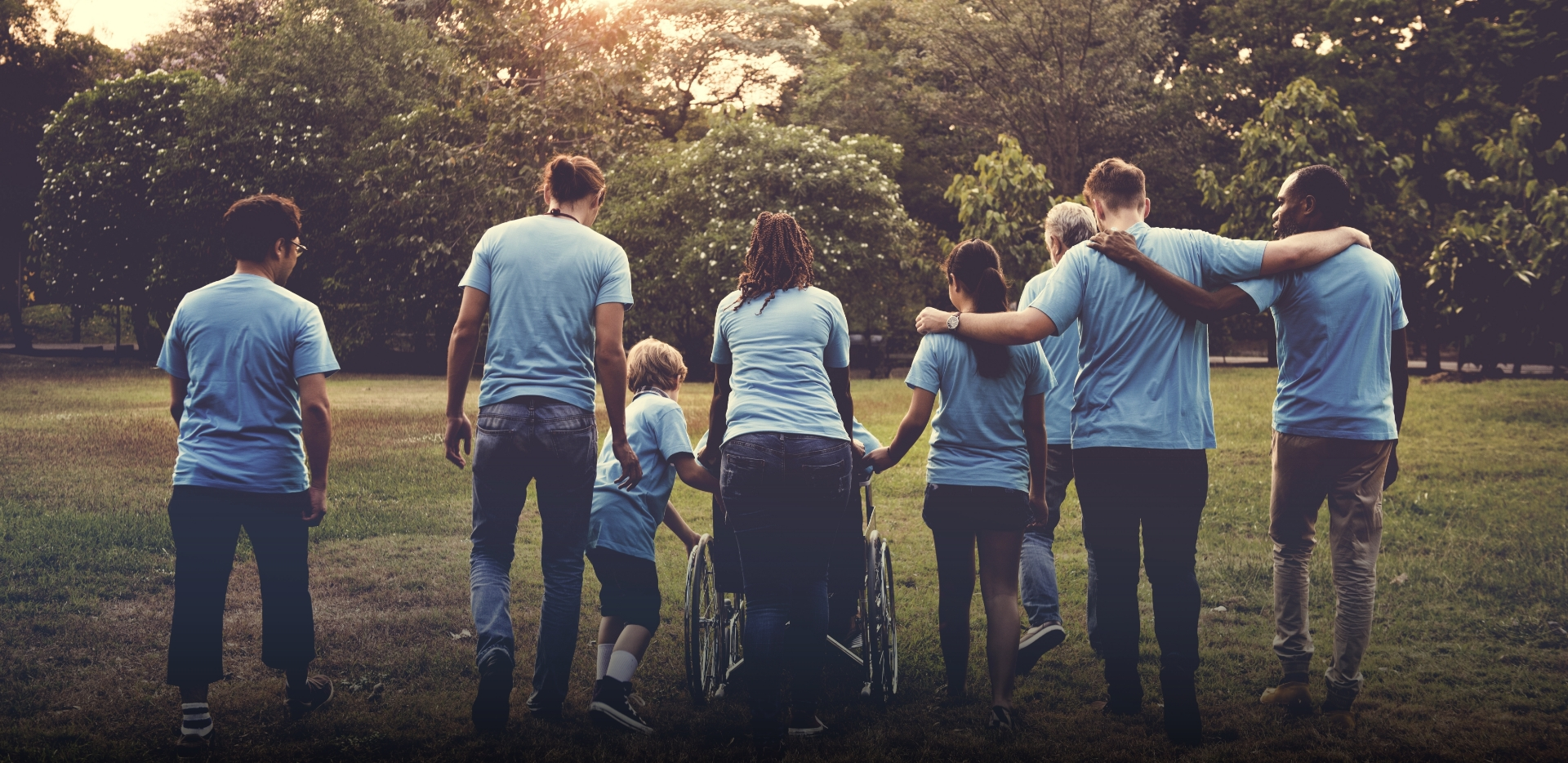 group of supportive friends and family wearing matching t-shirts push person in wheelchair across a field at a park