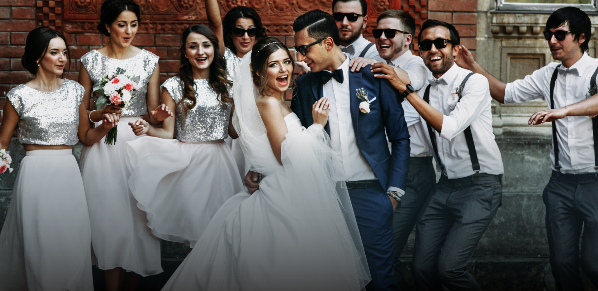 happy bride and groom surrounded by wedding party pose for photo