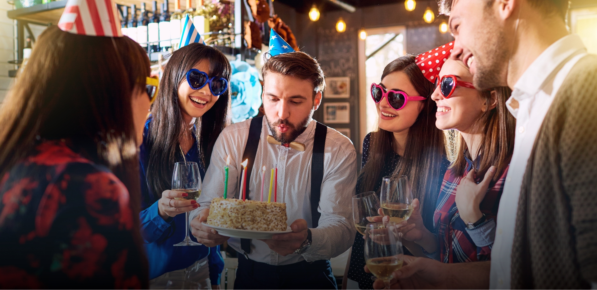 millennial man blows out candles on birthday cake surrounded by friends wearing party favors