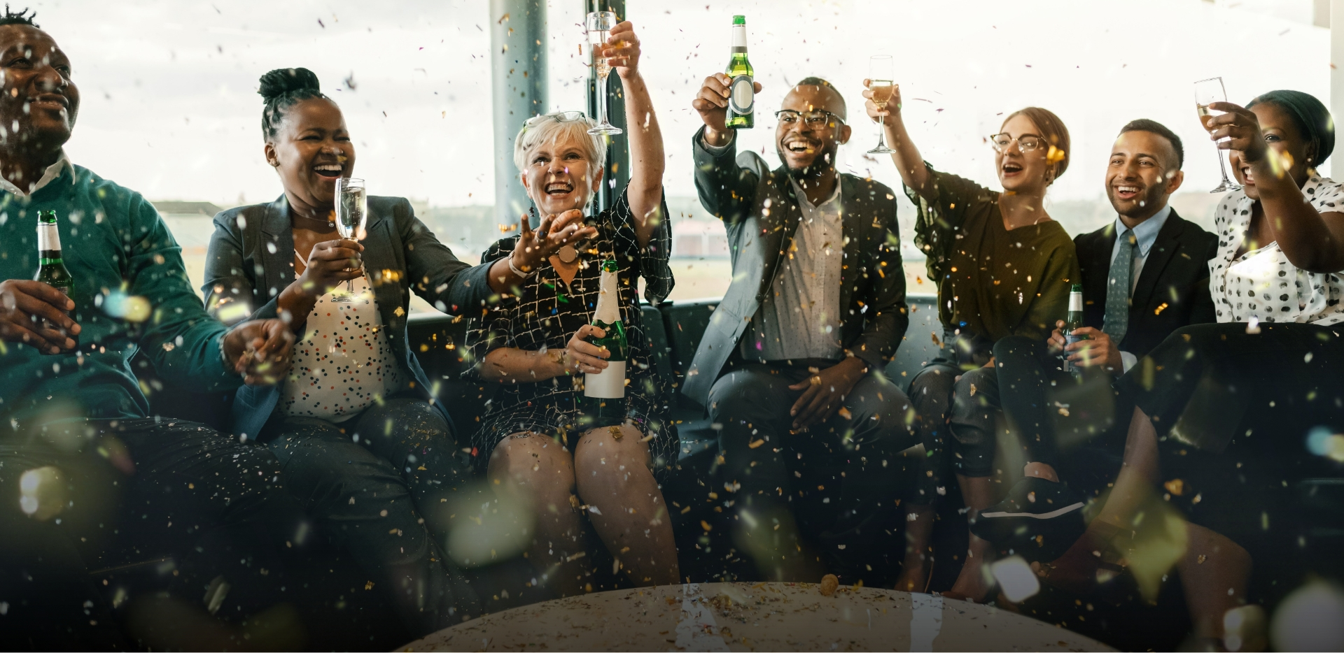 joyful colleagues toast a business achievement with champagne and confetti