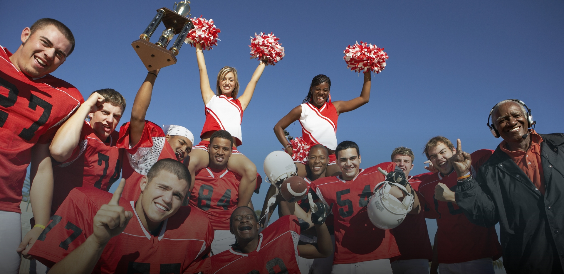 proud football players and cheerleaders with coach raise trophy to celebrate championship win