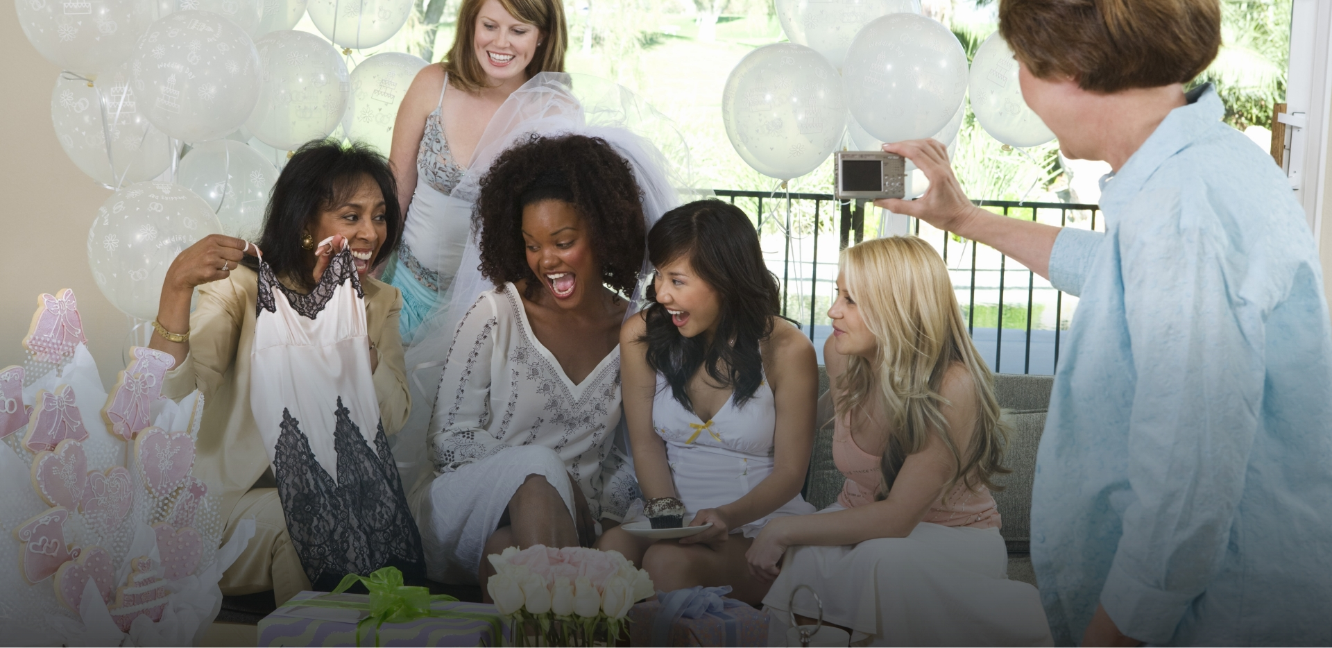 group of female friends and family look amused at risque gift at bridal shower