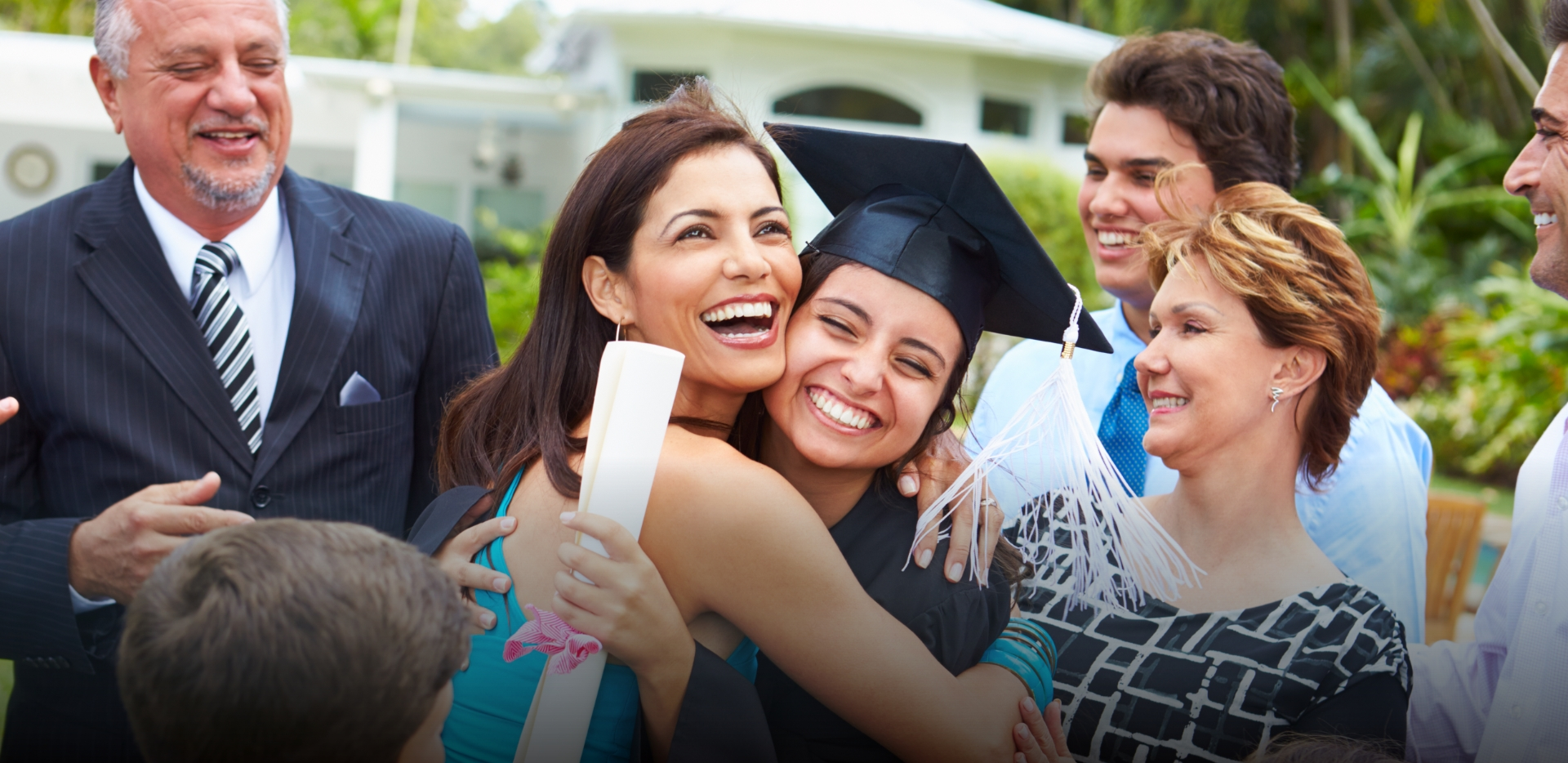 Hispanic mother hugs daughter wearing cap and gown and holding diploma after college graduation ceremony while happy family encircles them