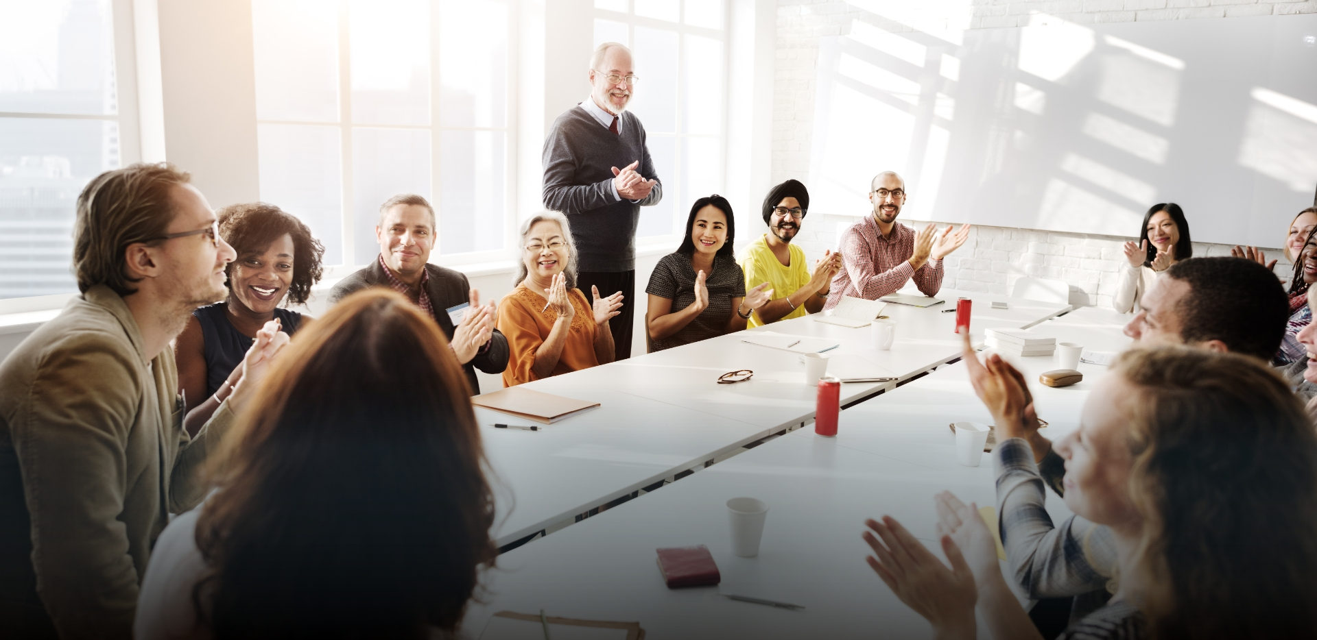 a dozen colleagues seated around conference room table encourage and elevate a humble coworker's contribution