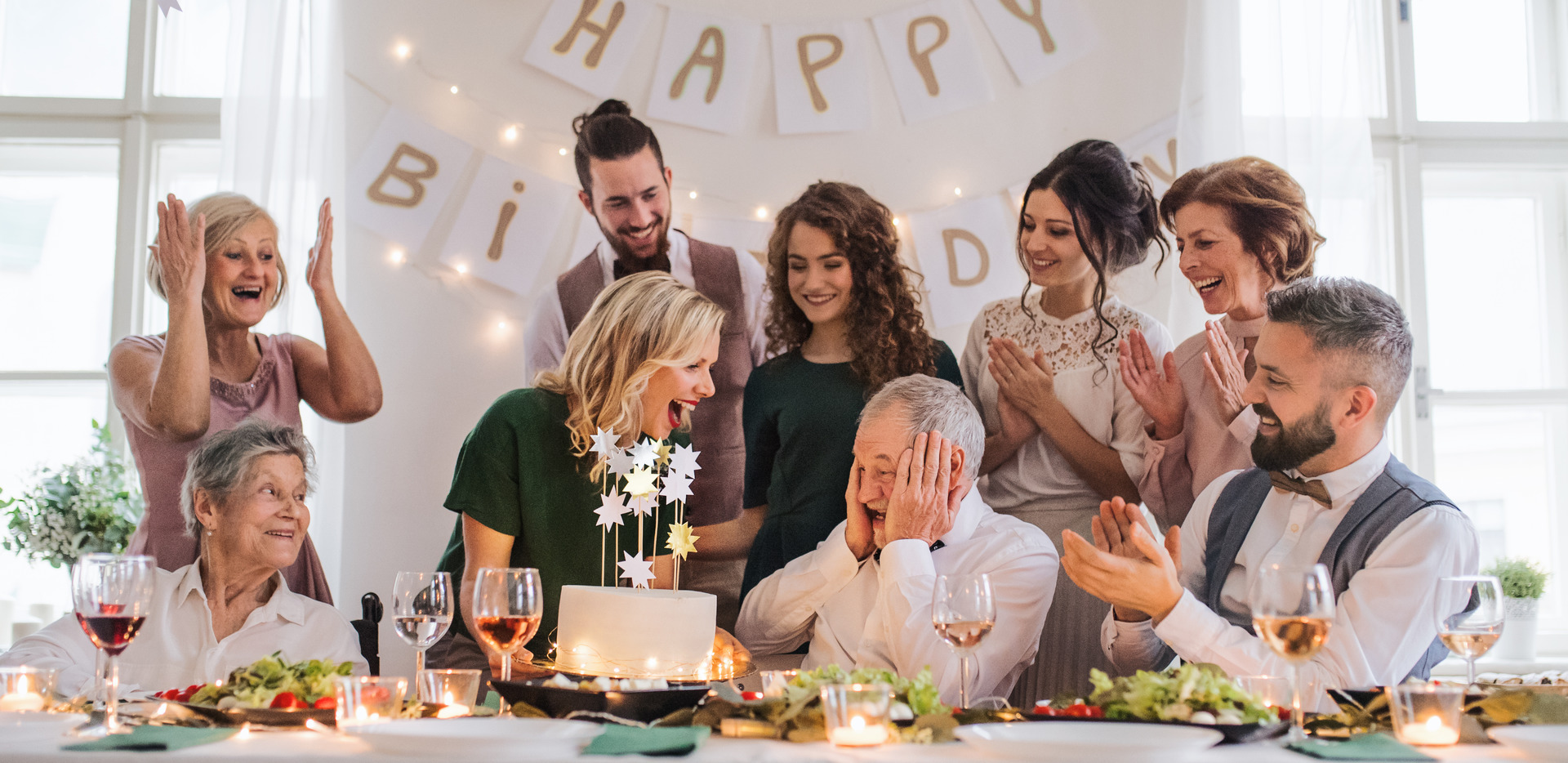 grandfather shows elated surprise as daughter brings cake with sparklers and stars to the banquet table while the rest of the family applauds and cheers; festive happy brithday banner, twinkle lights and candles decorate the room